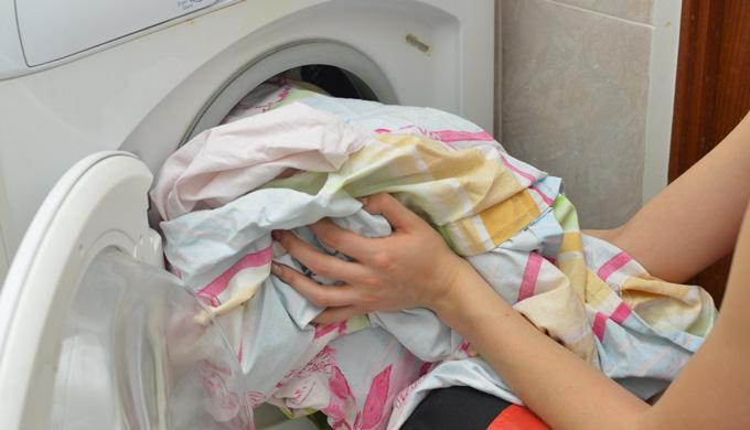 洗濯機に衣類を入れている女性